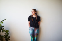 woman in yoga pants leaning against a white wall