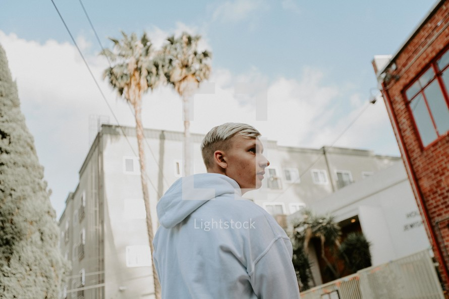 blonde young man walking and tall palm trees