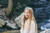 smiling child in front of a waterfall