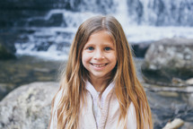 smiling child standing in front of a waterfall