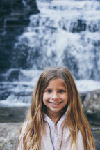 smiling girl standing in front of a waterfall
