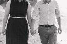a couple holding hands walking on a beach