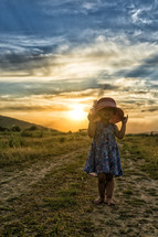 little girl in a hat at sunset on a dirt road