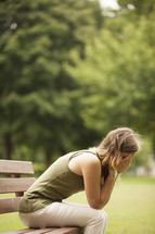 Worried woman sitting on park bench.