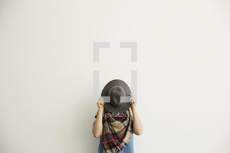 a woman hiding behind a hat