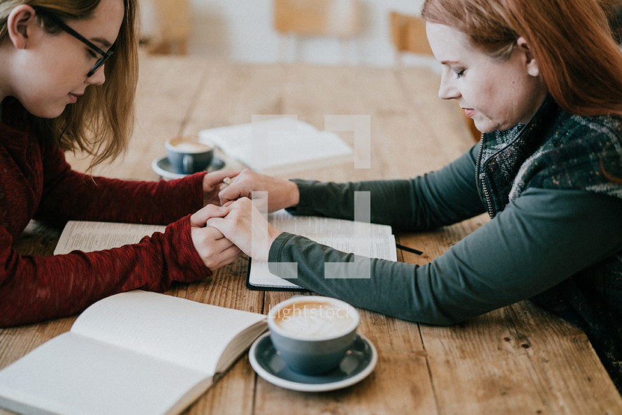 women at a fall Bible study holding hands praying