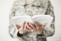 Female soldier in uniform holding a Bible.