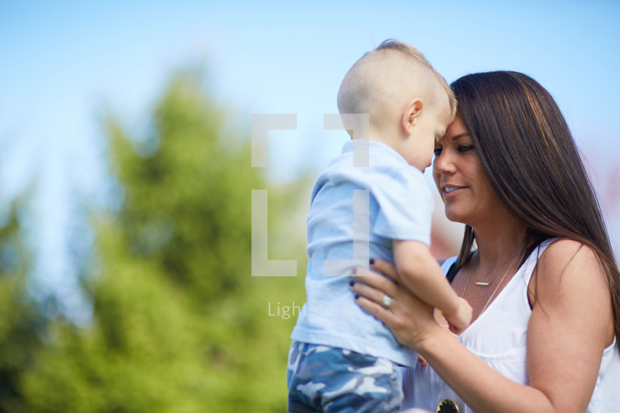 a mother holding her son outdoors