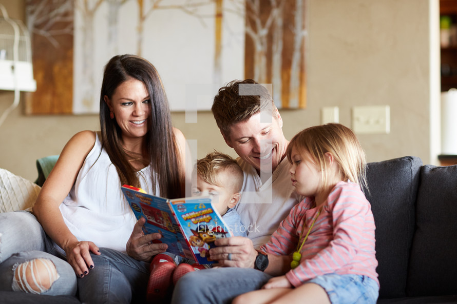 a mother and father reading a book to their kids