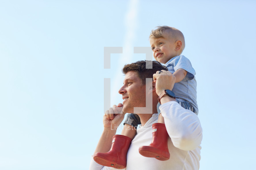 a toddler boy on father's shoulders