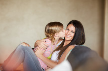 a little girl kissing her mom on the cheek