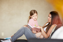 a mother and daughter reading a book together