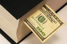 one hundred dollar bill bookmark in a Bible