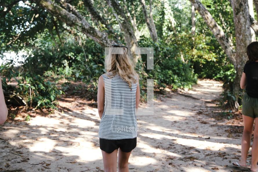 woman walking into a coastal jungle