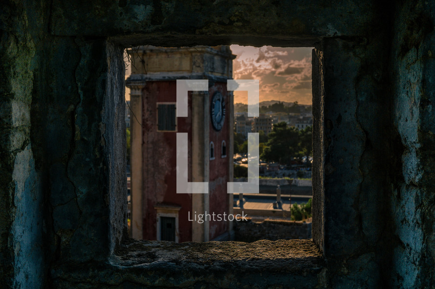 view of a bell tower through an old window cutout