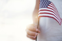 Child's hand holding an American flag.