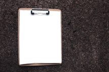 blank clipboard hanging on cork board wall