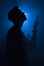 a man holding a cross illuminated in darkness
