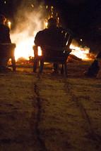 Man drags a Muskoka chair across a beach towards a large bonfire.