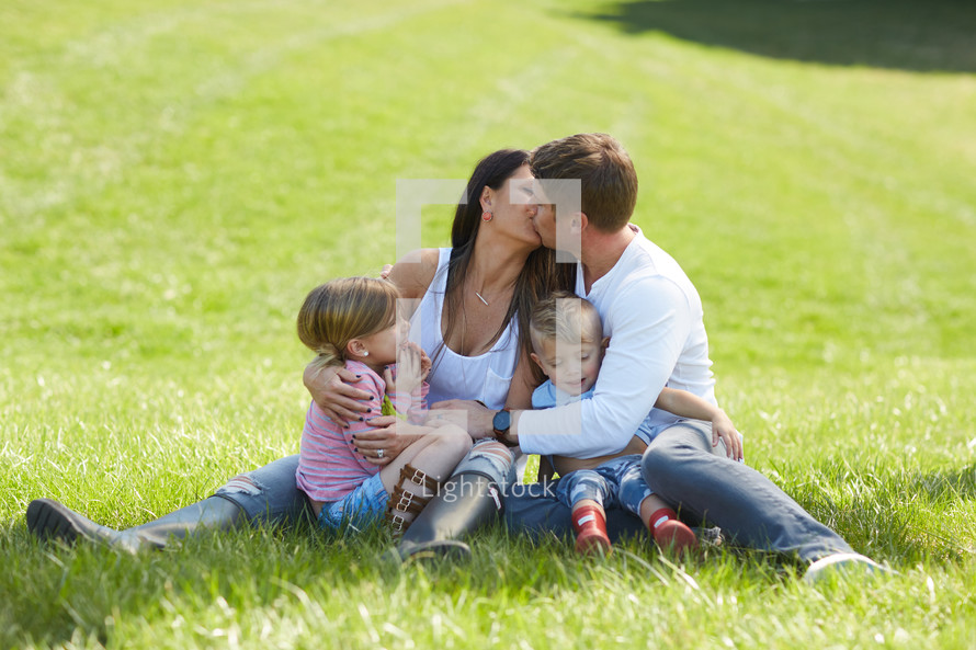 a loving family sitting in the grass
