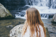 child standing in front of a waterfall