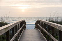 Beach boardwalk  leading down into the ocean at daybreak.