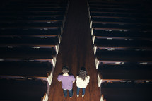 Couple standing int he aisle of a dark ,empty church.