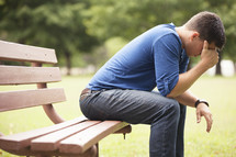Worried man sitting on park bench.