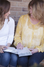 A mother and daughter reading a Bible together