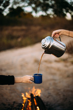 pouring coffee from a coffee pot into a mug over a campfire