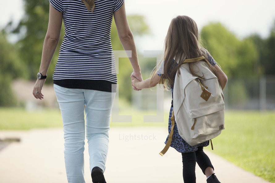 a young girl holding hands with mom walking to school