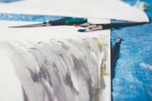 paper, paint brushes, scissors, paint, tarp, making signs