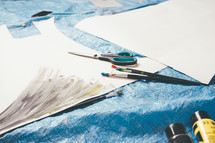 paper, paint brushes, scissors, and paint on a tarp