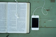Iphone and earbuds on a wooden table with an open Bible.