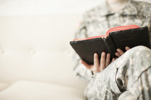 Female soldier in uniform sitting on a sofa reading a Bible.