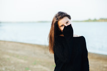 a teen girl covering her face with her sleeve