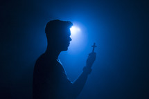 silhouette of a man holding a cross illuminated in darkness