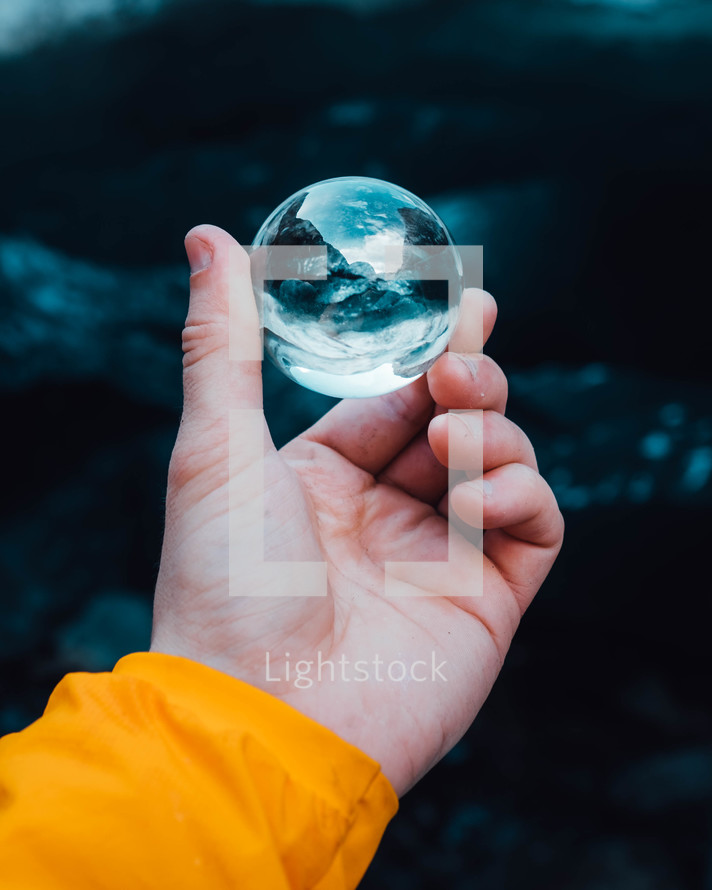 hand holding a glass orb