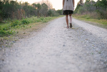 woman walking on a gravel road
