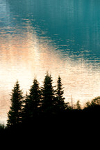 silhouette of trees and glistening lake water