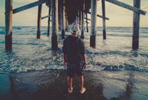Young man standing under a pier | Contemplation | Watching Waves | Facing Forward | Standing | Back | Outside | Looking Out | Vision | Perspective | Landscape | Nature | Creation | Person | Male | Youth | Generation | Reflection