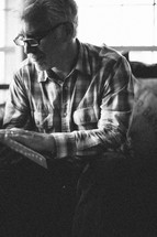 elderly man sitting reading a Bible
