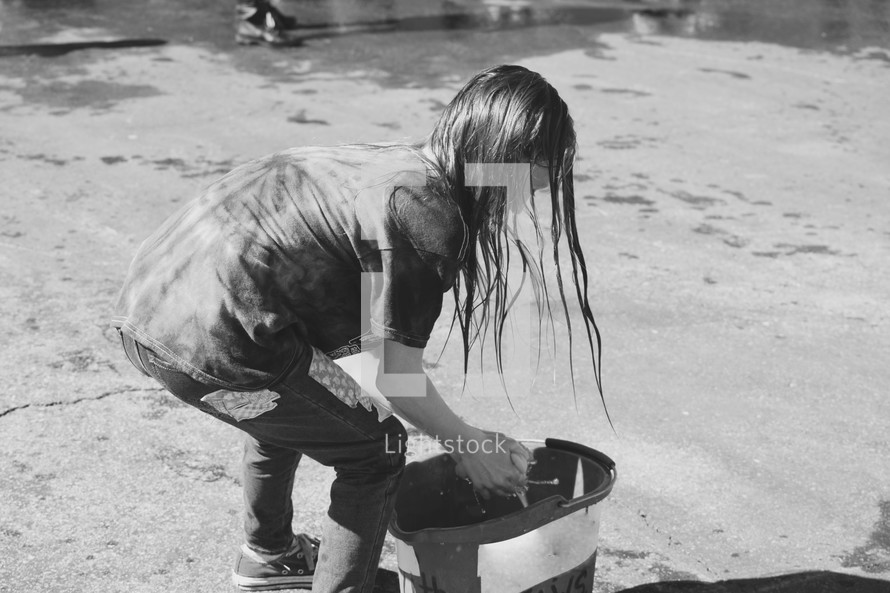 girl wetting a sponge in a bucket for a car wash