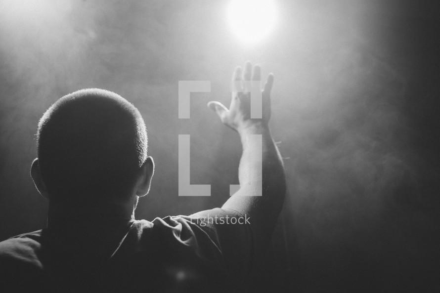 man with raised hand