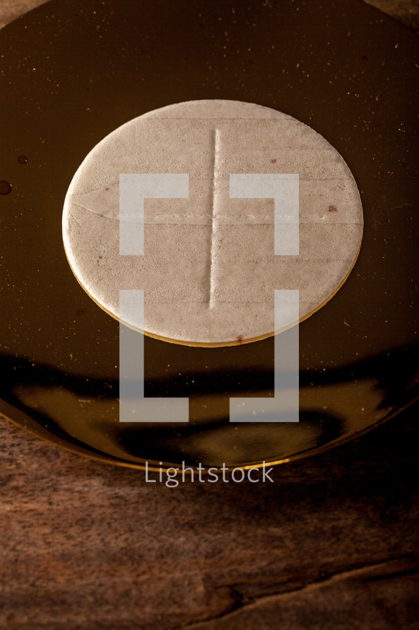 A communion wafer on a golden plate.