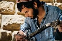 man tuning an instrument