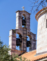 View of the Holy Trinity church bell tower from the narrow streets of Old Town Budva, Montenegro