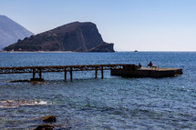 Two fisherman attempt to catch fish at the end of a pier on Olt Town Beach in Budva, Montenegro