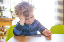 a toddler boy playing on a cellphone
