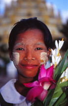 Burmese woman with painted face and tropical flowers outside a Buddhist temple